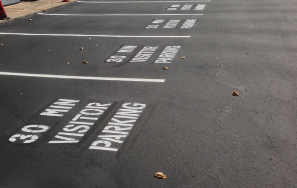 asphalt-parking-lines-spray-painted-stencil